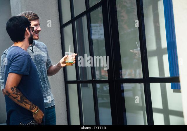 Male couple looking at city shop window - Stock Image