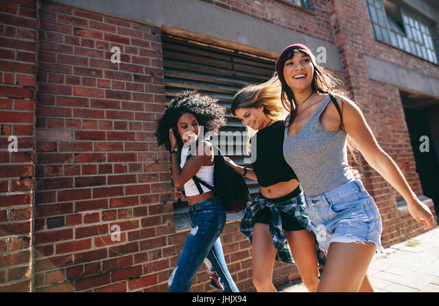 Multiracial group of friends walking down the city street. Three young women walking outdoors on road. - Stock Image
