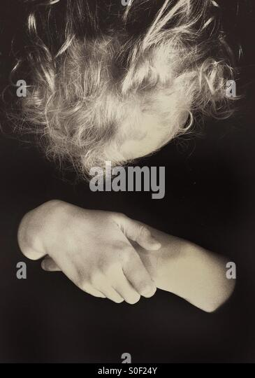 Young girl looking down at her folded hands - Stock Image