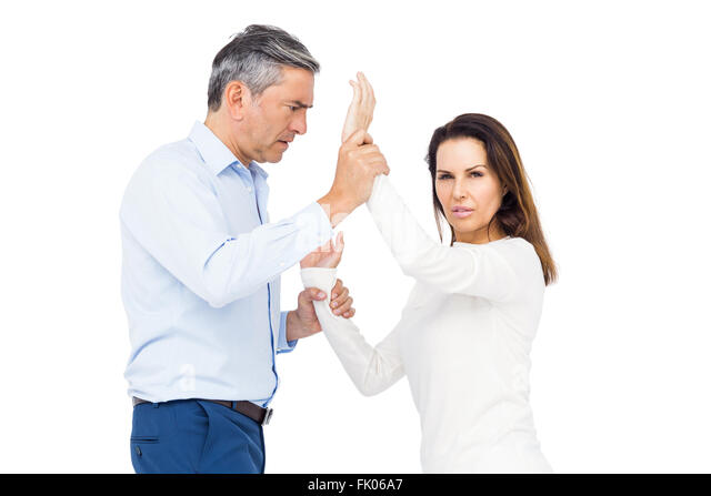 Violent man grabbing wifes wrists - Stock Image