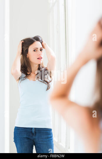 Woman checking her face in the mirror. - Stock Image