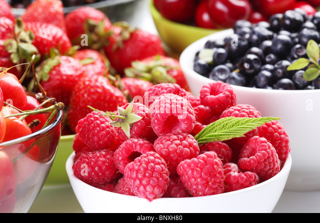 Different berries in bowls. Bowl with tempting raspberries in a front. - Stock Image