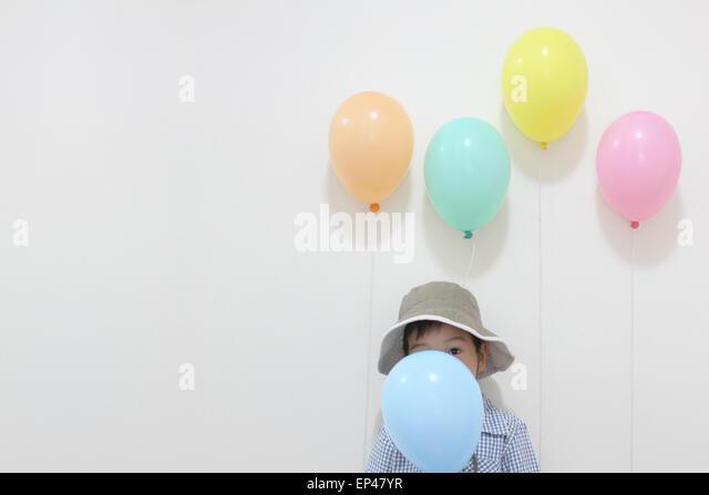 Boy hiding behind a party balloon - Stock Image