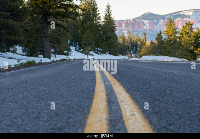 Looking Down Curve of Yellow Strip on Snowy Mountain Road in late winter - Stock Image