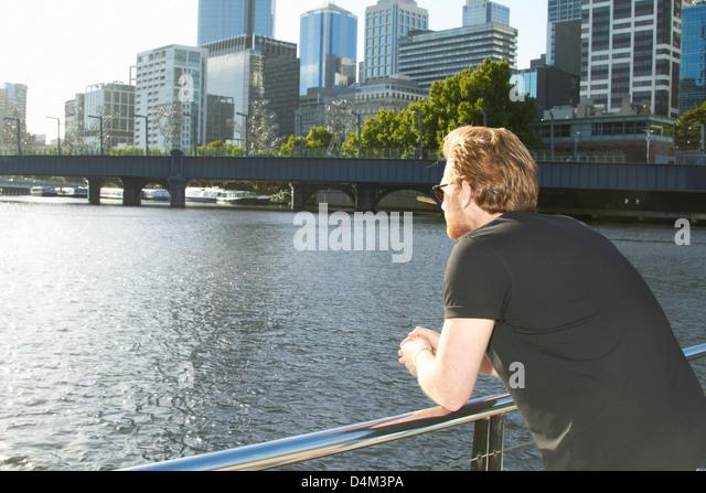Man overlooking urban river on bridge - Stock Image