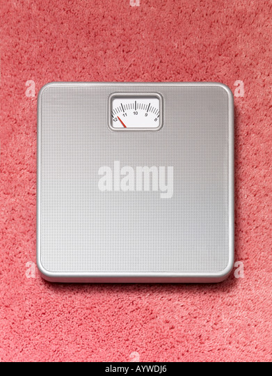 A Bathroom weighing scales on a pink fluffy carpet - Stock Image