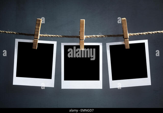 Blank instant print transfer photographs hanging on a clothesline - Stock Image