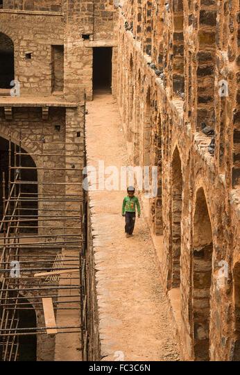 A local boy walking inside the Ancient underground step-well (Ugrasen ki Baoli) in heart of New Delhi, India. - Stock Image
