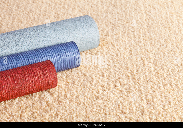 Sample rolls of wallpaper on a light coloured carpet, with copy space. - Stock-Bilder