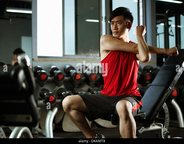 Man sitting on weight bench drinking stretching to warm up - Stock Image