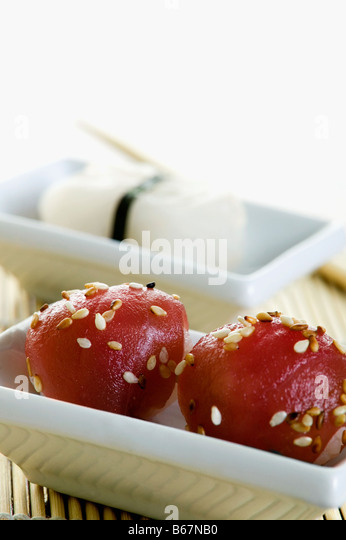 Balls of tuna fish with sushi in the background - Stock Image