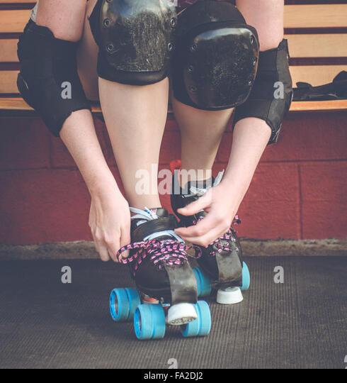 Roller derby, roller skating woman outside of roller rink with roller skates on. - Stock Image