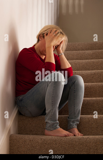 Woman head in hands sitting alone. Model and property (owned by photographer) released. - Stock Image