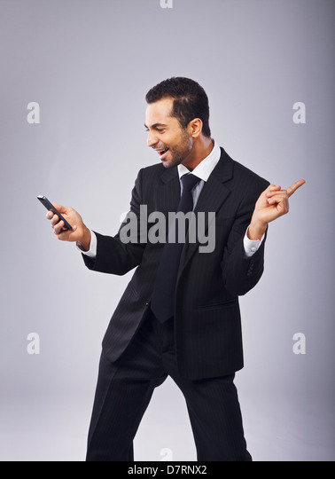 Young businessman with phone dancing out of joy - Stock Image