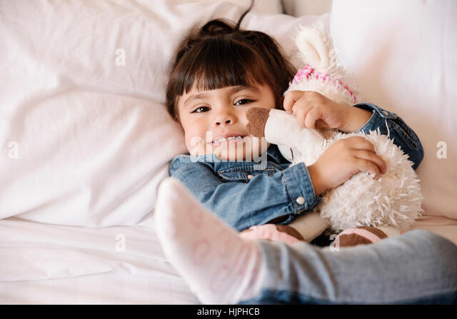 Smiling child girl with her teddy at home. - Stock Image
