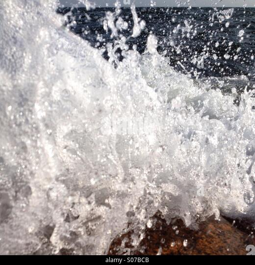 A wave breaking on rocks captured at the last moment before it hits the lens - Stock Image