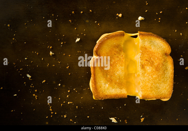 A Grilled Cheese Sandwich cut in half pulling the cheese on a wood table - Stock Image