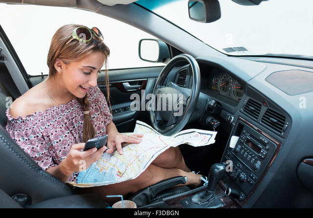 Woman checking phone in car with map on lap - Stock Image