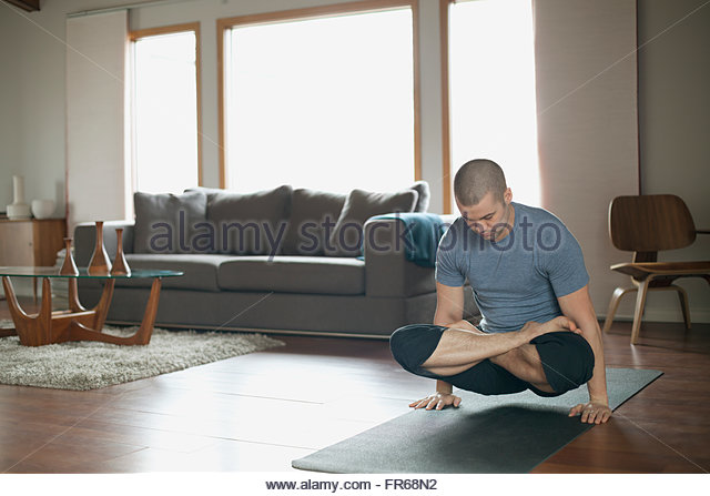 man doing yoga poses at home - Stock Image