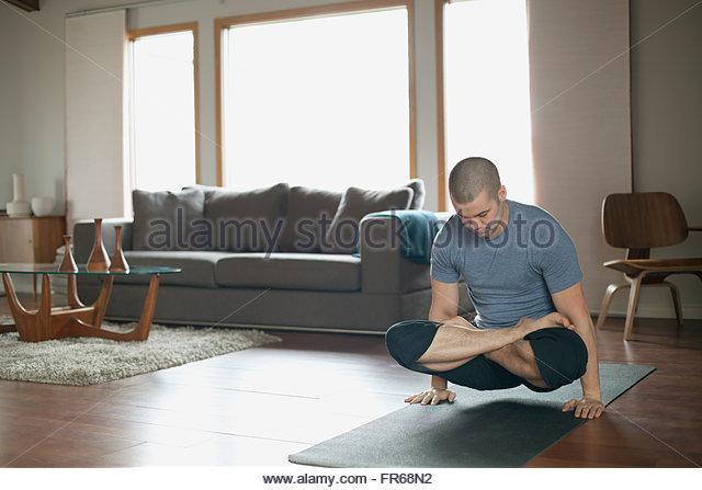man doing yoga poses at home - Stock Image
