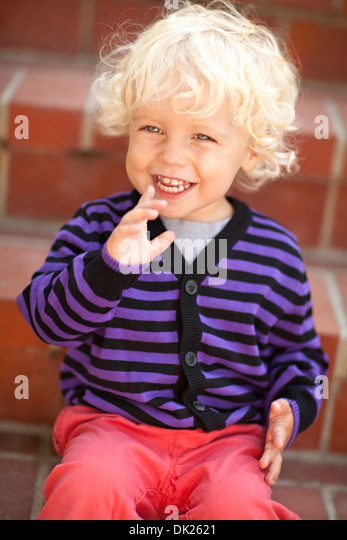 Close up of tilt blonde toddler boy with curly hair laughing on steps - Stock Image