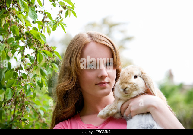 A young girl holding her pet rabbit - Stock Image
