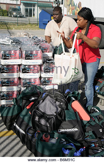 Miami Florida Little Haiti Thanksgiving Turkey Give-Away give away volunteers Black Haitian man woman packing bags - Stock Image
