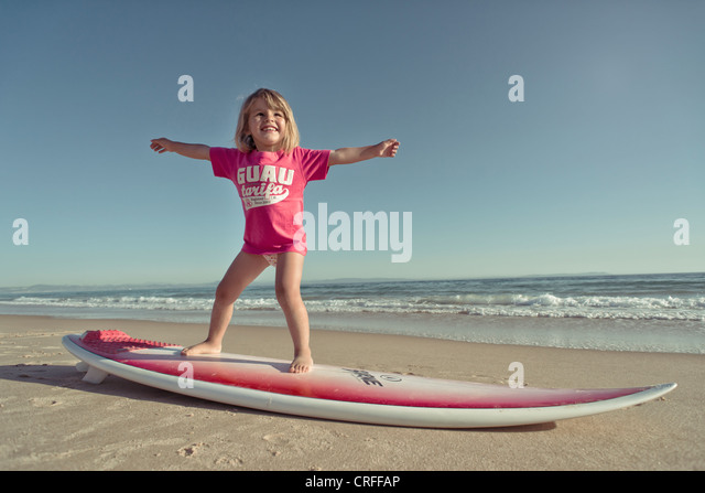 Young girl surfing at the beach. - Stock Image