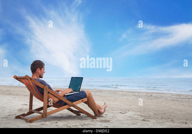 businessman working with computer on the beach - Stock Image
