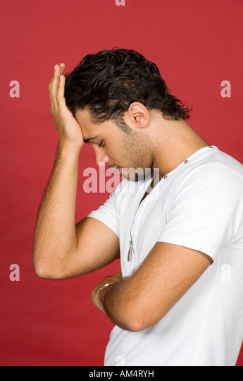 sad young man hand on head - Stock Image