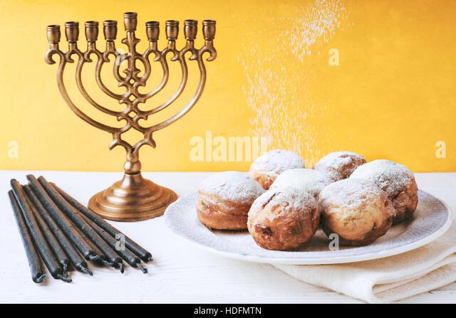 Hanukkah menorah and sufganiot on the table horizontal - Stock Image
