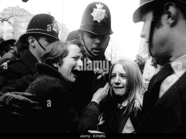 Upset Beatles fans crying because Paul McCartney got married are led away by police March 1969 - Stock Image