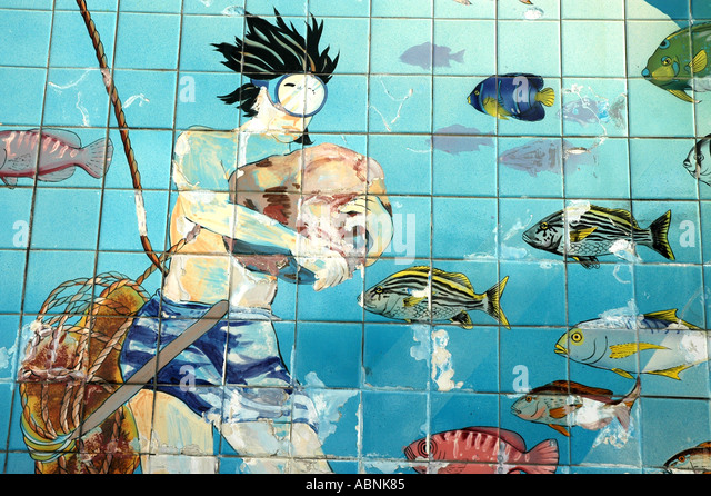 Tarpon Springs Florida Wall Tiles at the Sponge Exchange showing modern sponge diver picking up sponges - Stock Image