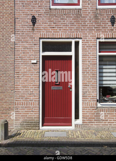 Red closed door in Alkmaar, Netherlands, Europe - Stock Image