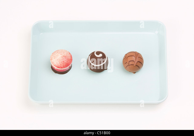 still life of three chocolate candies on a tray - Stock Image