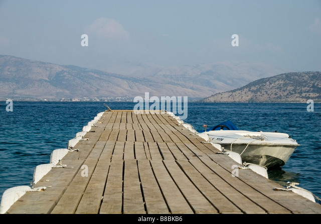 Close-up of jetty lined in white bumper tyres,  perspective leading to sea, Albanian mountains, Agni, Corfu, Kerkyra, - Stock Image