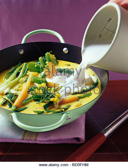 Pouring coconut milk into pan of Indonesian vegetables - Stock Image