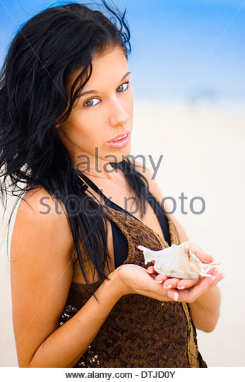 Attractive Young Female Holding Seashell With Expression Of Care As If Expressing Her Environmental Concern For - Stock Image
