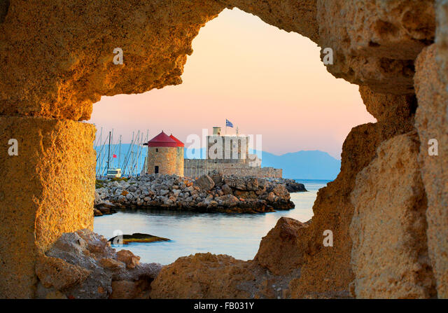 The Castle and old windmills at the enterance to Mandraki harbour in Rhodes, Greece, UNESCO - Stock Image