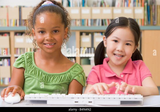 Two students in class at computer keyboard - Stock Image
