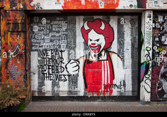Happy, smiling devil, greed and exploitation concept graffiti in Amsterdam, Holland, Netherlands. - Stock-Bilder