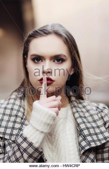 Young woman signaling Shhh - Stock Image