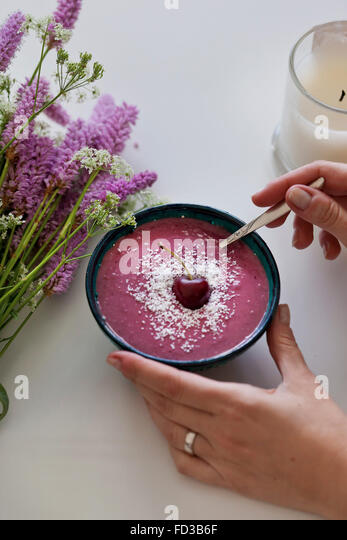 Pink Cherry and coconut smoothie in a bowl, topped with shredded coconut and fresh cherry, purple and white flowers - Stock Image