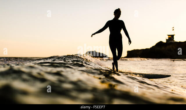 Silhouette of a woman surfing, Malibu, California, USA - Stock Image