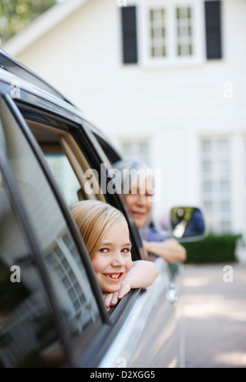 Older woman and granddaughter leaning out car windows - Stock-Bilder