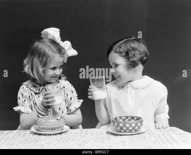 1930s TWO SMILING LITTLE GIRLS DRINKING MILK BOWL OF CEREAL TALKING LAUGHING EATING - Stock Image