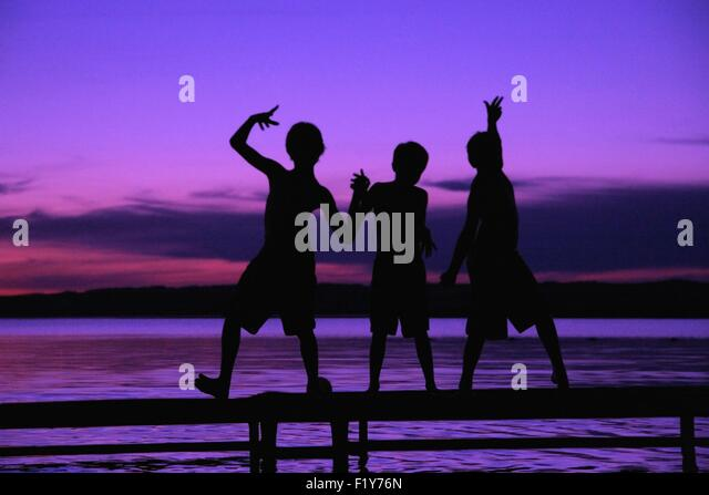 Three Silhouettes Of Boys On A Dock Against A Sunset - Stock Image