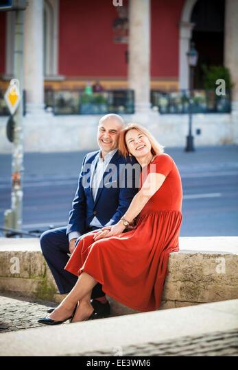 Happy senior couple sitting by street, Munich, Bavaria, Germany - Stock-Bilder