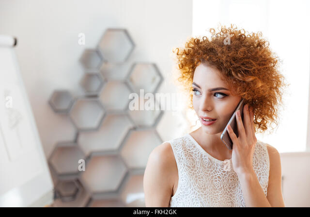 Pensive beautiful young business woman talking on cell phone in office - Stock Image
