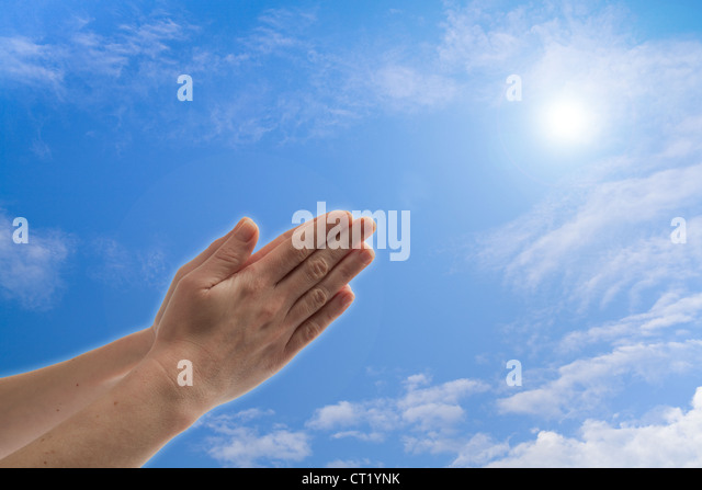Praying hands against blue sky with clouds - Stock Image